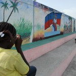 The murals along a wall in Cite Soleil are a source of pride, and Nadege shoots a portrait to incorporate them in her work.